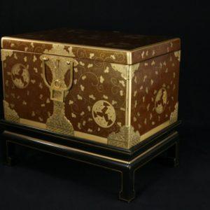 La structure en bois ainsi que les bronzes de ce coffre sont du XIXème siècle. Le décor en laque brune et or est une création des Ateliers Brugier (Julie Lecreps) Dimensions : H.37cm x L.63cm x P.42cm