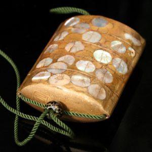 Inro en laque d'or et incrustations de nacre à décor de fleurs.