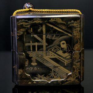 Inro noir et or à décor d'un homme accoudé sur une table
